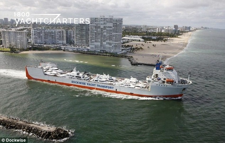 Aerial photograph of a ship that transports superyachts. It is headed down a canal, and there is a tugboat next to it. There are buildings in the background, as if the ship is pulling in to a city.