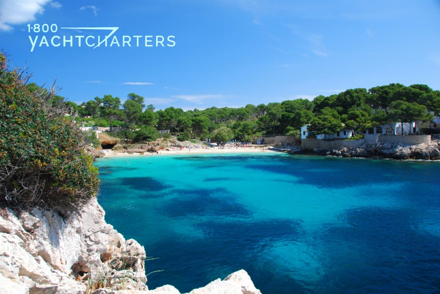 Photograph of the coastline of Mallorca. Turquoise water with dark patches of deep blue. Rocky coast. Sand beach.