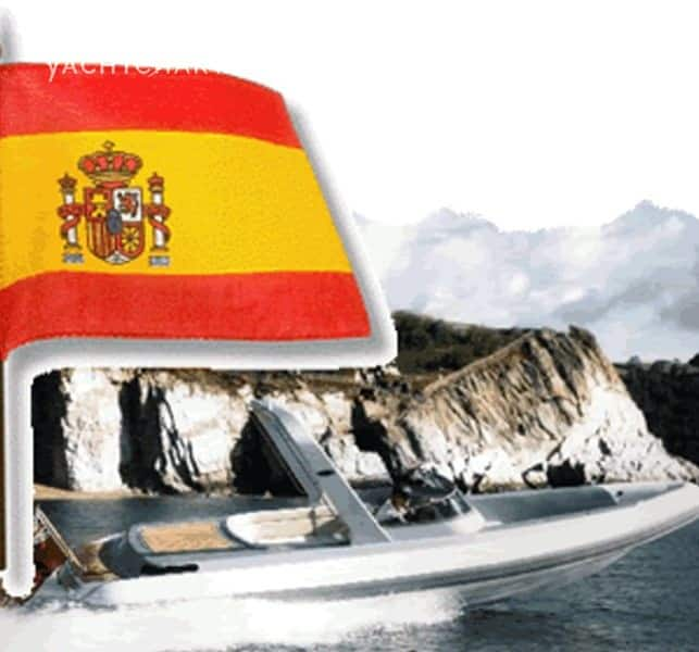 Photograph of an inflatable boat with a Spanish flag overlaid on top of the photo. Rocky coastline in the background.