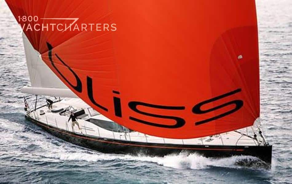 Aerial photograph of sailboat, Bliss, underway. She is heading toward the lower left side of the picture, and she is leaning toward the front of the photo. Her red sail with black lettering that says, BLISS, is full and puffed out toward the front of the photo, obscuring most of the yacht except for the waves underneath the dark hull and a few parts of the white superstructure of the boat