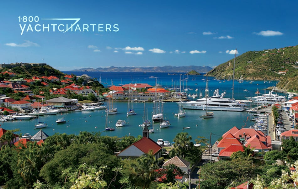 Photograph of the marina in St. Barths in the Caribbean.  Basin is full of sailboats and powerboats of all sizes and colors.  Mountains surround the marina on 3 sides