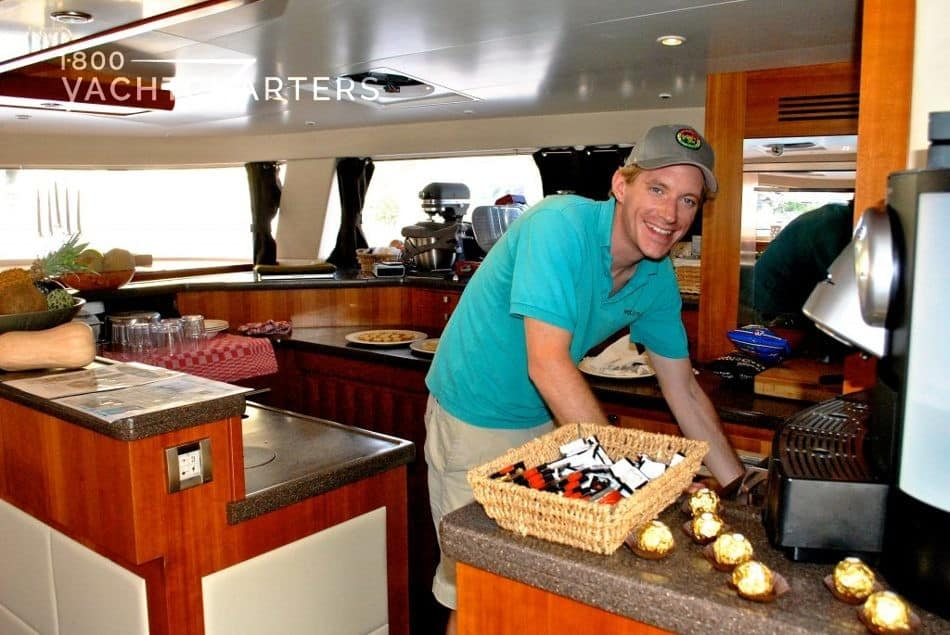 Photograph of Chef Rene Kappetein award-winning superyacht cook smiling in the galley of a yacht. He's wearing a teal t-shirt, khaki pants, and a khaki baseball cap.