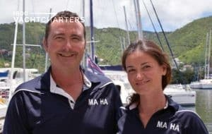 Photo of crew of catamaran sailboat, Ma Ha. Man on the left. Female on the right. Both are wearing black short-sleeved polo shirts that say Ma Ha on them. They are both smiling at the camera.
