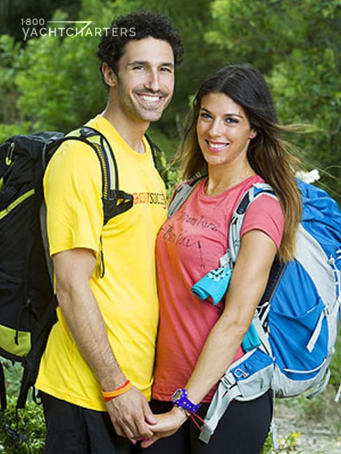 Photograph of Ethan Zohn and Jenna Morasca of Amazing Race. They are standing, facing each other, holding hands. He is on the left, and she is on the right. Both are in center of photo.
