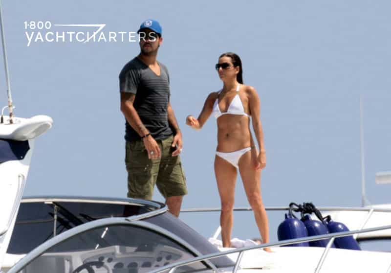 Photograph of Educardo Cruise and Eva Longoria on the deck of a boat. the sun is shining, so they are both wearing sunglasses. She is on the right, in a white bikini. He is on the left, in a blue baseball cap, grey t-shirt, and dark khaki shorts. They are looking to the left of the photo.