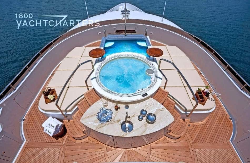 Aerial photograph of top deck of motoryacht Mi Sueno. There is a bright blue hot tub in the center of the deck.