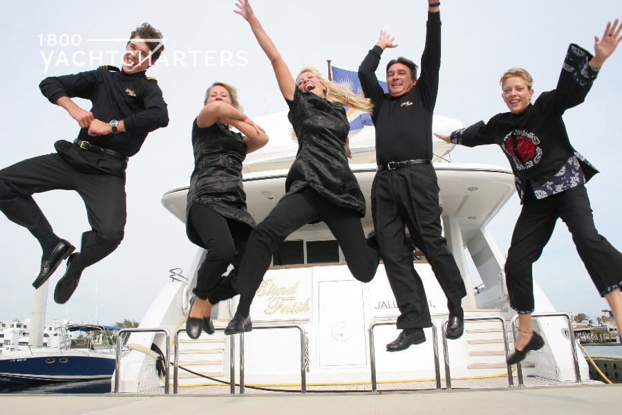 Photo of 5 yacht crew members on the deck of a white motoryacht. All 5 are jumping in the air and making funny faces and poses.  All are wearing solid black outfits with an Asian theme.