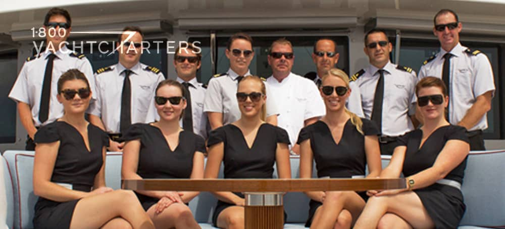Photograph of professional yacht crew on back of motoryacht. Professional photo. Men in white standing in background.  Women in black dresses seated in front row.