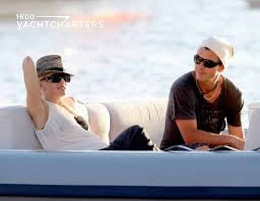 Photograph of Gwen Stafani and Gavin Rossdale relaxing on a yacht. The photo does not include any background details. It's just a photo of the two of them on a white boat, seated on plush white seating. Gwen has her right arm propped above her head and is wearing a sun visor.  Gavin is wearing a cap on his entire head. Both are in dark sunglasses
