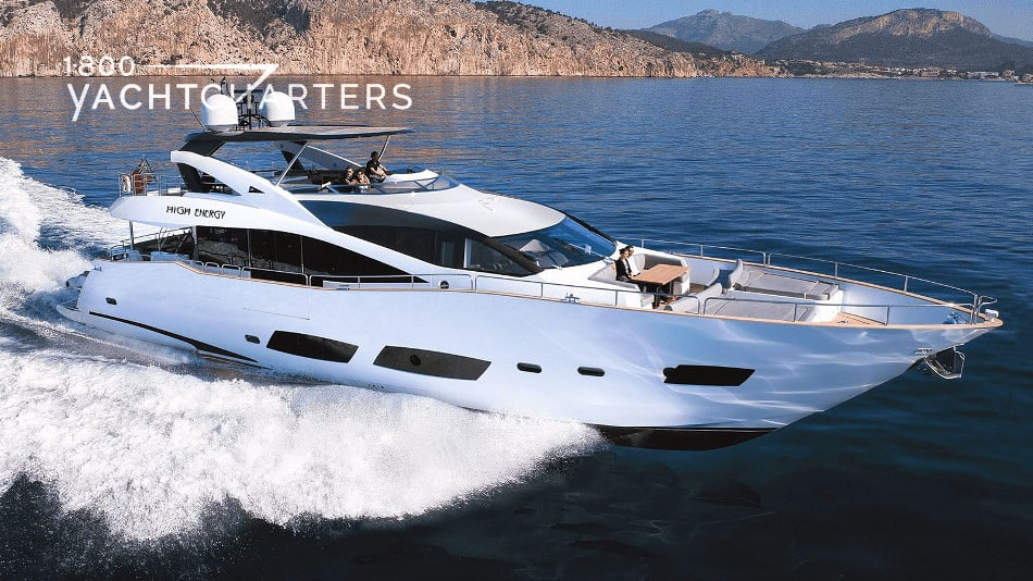 Photograph of the sunseeker 28 model yacht underway. White yacht. Moving quickly. Large waves underneath the boat, hitting the bow and bottom. Glassy sea. Rock mountain in background - mediterranean.