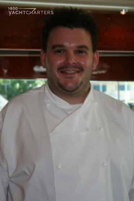 Photograph of Chef Geoffrey Fisher. He is on a boat. He is wearing a white chef's coat. He has a big smile.