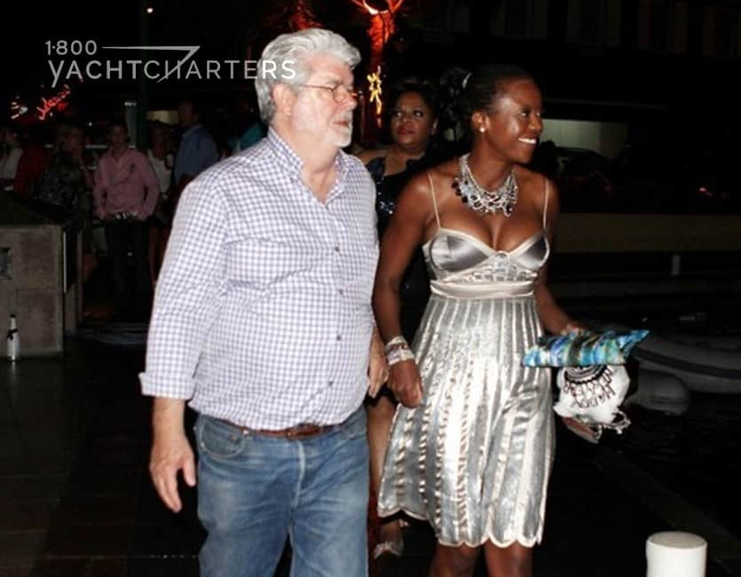 Photograph of George Lucas and his wife walking in a yacht marina. She is wearing a shiny silver cocktail dress. He is wearing jeans and a short-sleeved button down shirt.