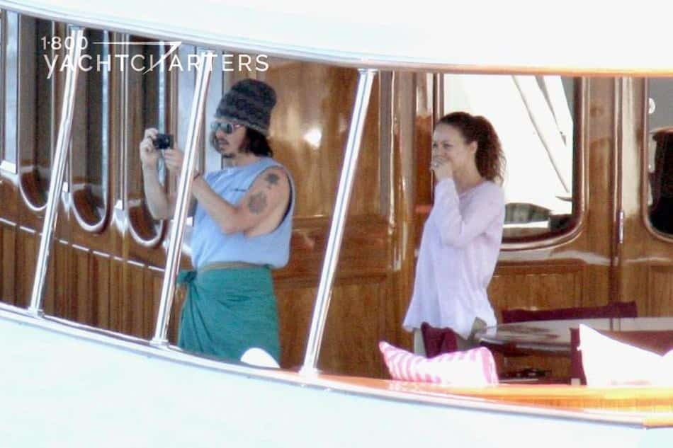 Photograph of Johnny Depp and Vanessa Paradis on a yacht. Johnny is at the left of the picture. He is taking a photo. Vanessa is standing next to him, on the right, watching what he is doing. They are casually dressed. He is wearing green shorts, a light blue sleeveless t-shirt that shows his arm tattoo, and a bandana on his head. She is wearing a pink long-sleeved shirt, and her hair is pulled back in a ponytail. The yacht is white with brown shiny wood interior.