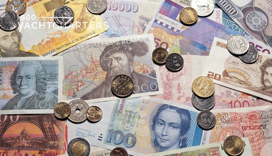 Photograph of money from different countries spread across the floor. Both paper bills and coins.