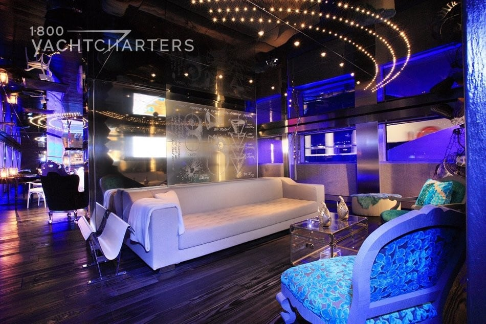 Photograph of main salon seating on yacht Sea Force One. It has trendy lighting that is like a nightclub. The lighting is very purple and blue. It glows over the white couch in the salon. The couch is located in the center of the photo.