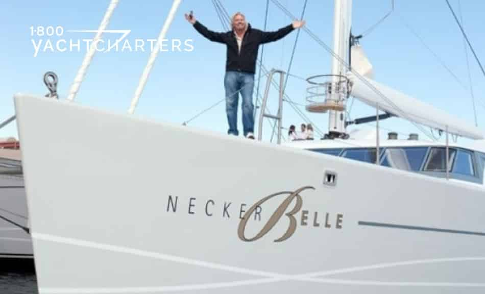 Photograph of Sir Richard Branson on the deck of catamaran Necker Belle. He is standing with his arms wide open and smiling at the camera. The yacht is aimed toward the left side of the photo.