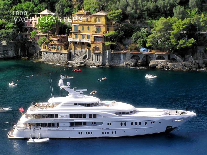 Aerial photograph of a big white boat at anchor in Amalfi. There are colorful homes dotting the mountainside in the background. The yacht is pointing toward the right side of the picture.