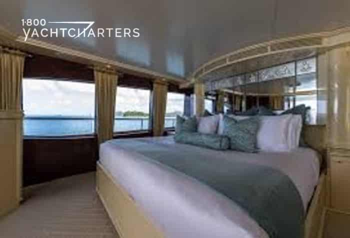 Photograph of a guest double stateroom on yacht, Touch. It is a large bed with silky grey bedding. The room is surrounded by windows on 3 sides.