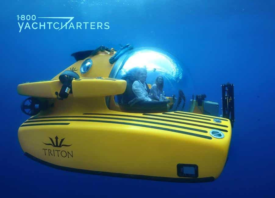 Underwater photograoh of a yellow Triton submarine with two people inside of it. It is headed toward the right side of the photo.