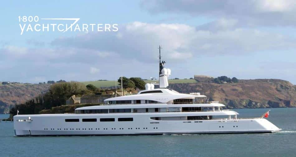 Profile photograph of solid white superyacht VAVA II. She is facing the left side of the photograph. There is a hill and green grassy area behind her. Looks like New England.