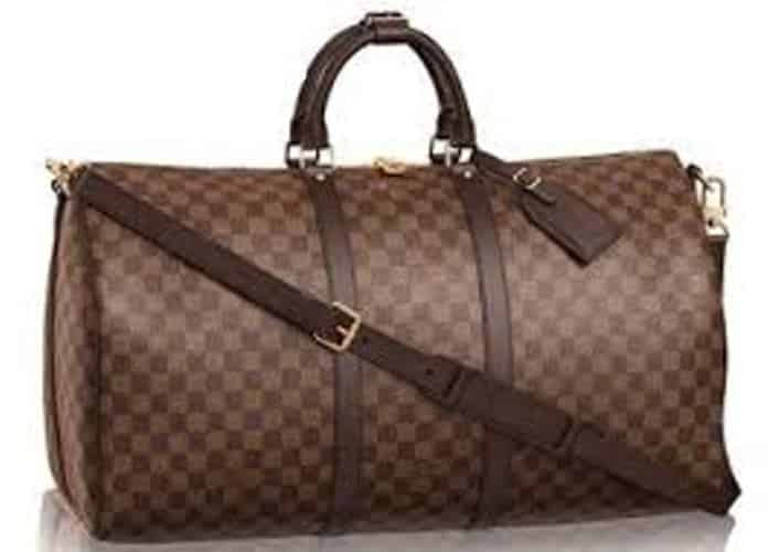 Photograph of a brown Louis Vuitton travel duffle bag with a white background.