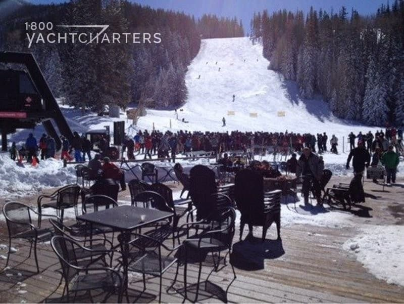 Photograph of a crowded ski slope. The photo is taken from the deck of a restaurant, looking up the mountain. There is a crowd of people waiting to ski in the snow.