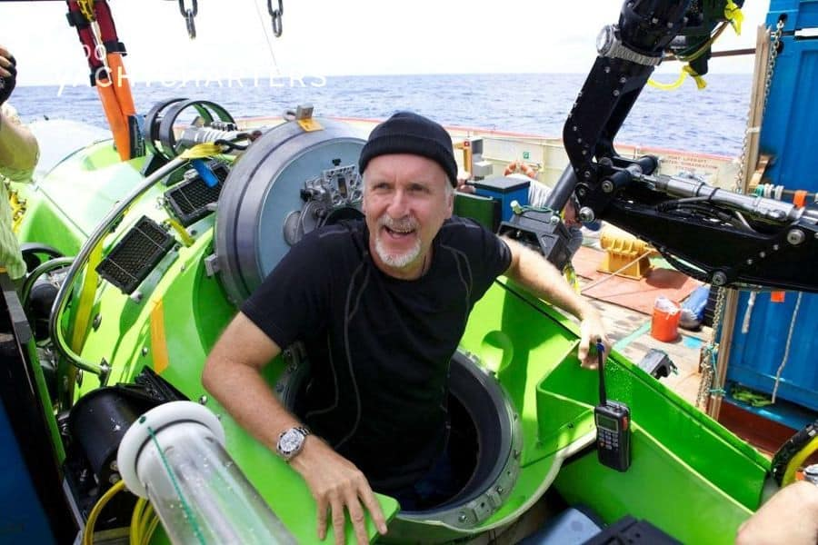 Photograph of James Cameron in a green and black submarine that is sitting on the deck of a boat. He is wearing a black beanie hat and a black short-sleeved t-shirt.  He has a white beard and a huge smile.