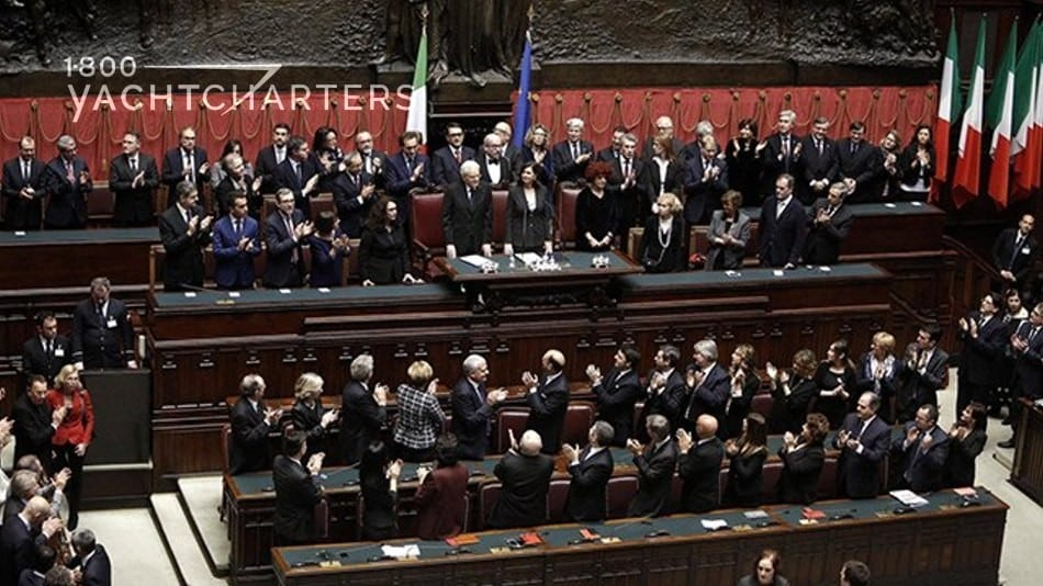 Photograph of the Italian government. Photo shows 6 levels of seating, as if an orchestra audience, full of men and women in dark-colored suits.