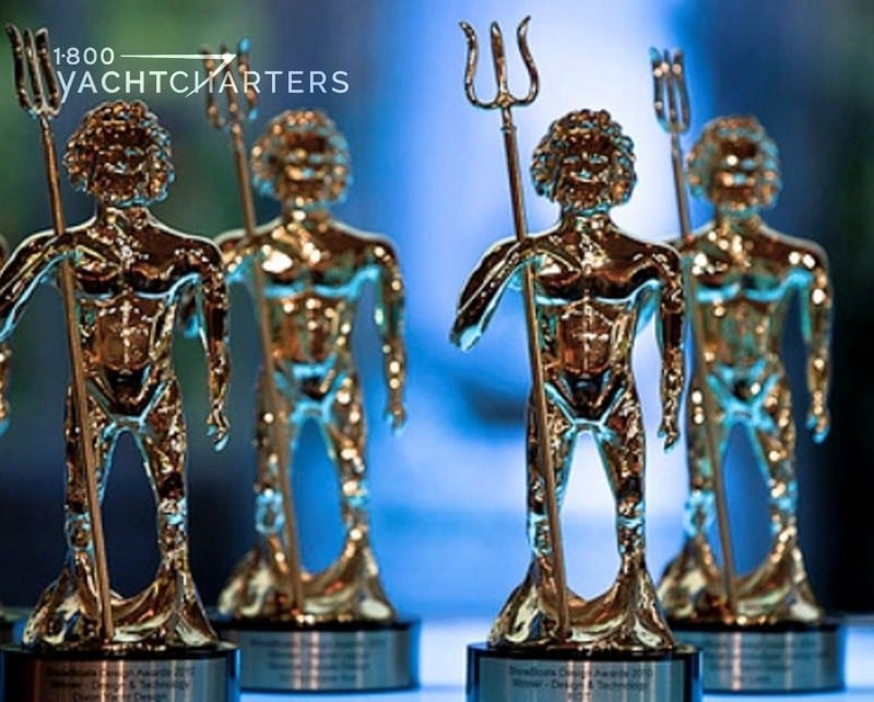 Photograph of Neptune award statues on a tabletop. There are 7 little statues on the table with a blue green background.