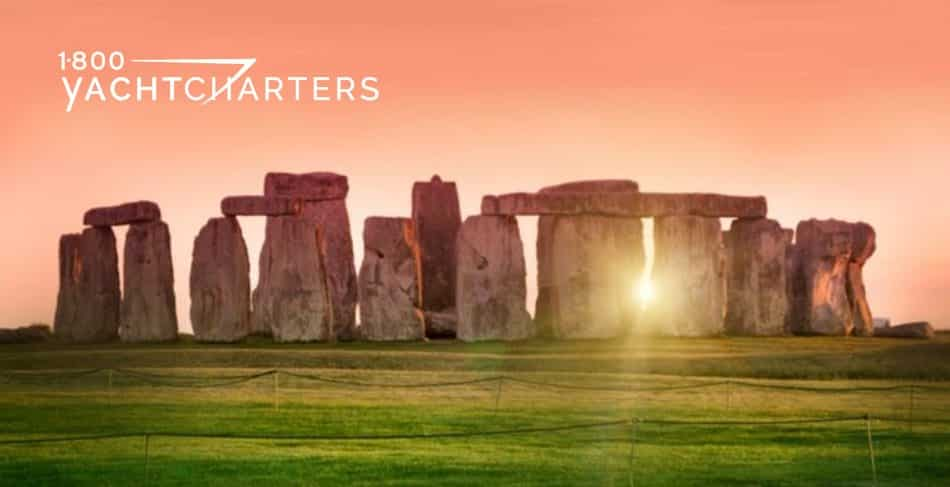 Photograph of the sunset shining through the rocks of Stonehenge. The sky is orange, and the grass is rich green.
