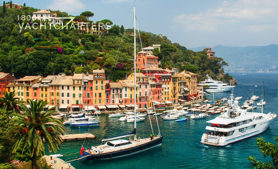 Photograph of Portofino, Italy marina. Green mountain in the background. Colorful red, yellow, and orange houses along the shoreline. Classic Portofino photograph. Dark turquoise water in harbor. Multiple sailboats and motoyachts anchored in the harbor.