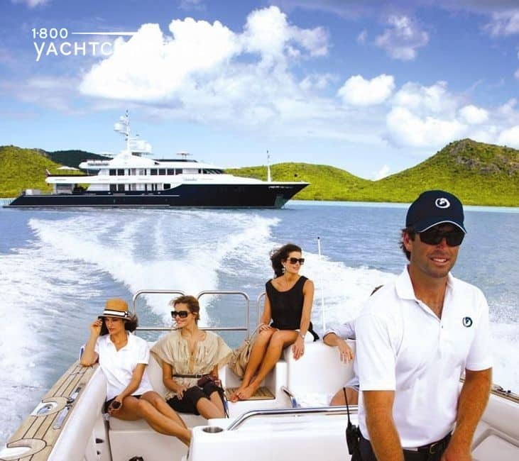 Photograph of three young women being shuttled away from a large blue superyacht (background) on a fast speedboat. A handsome, smiling mate wearing white polo shirt and navy baseball cap that matches the yacht colors, is driving the speedboat. There is a wake from the speedboat behind it that extends the width of the large yacht behind it.