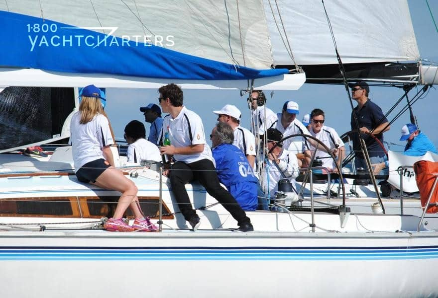 Profile photograph of a sailboat with kids and adults onboard. The sailboat is participating in a charity event.