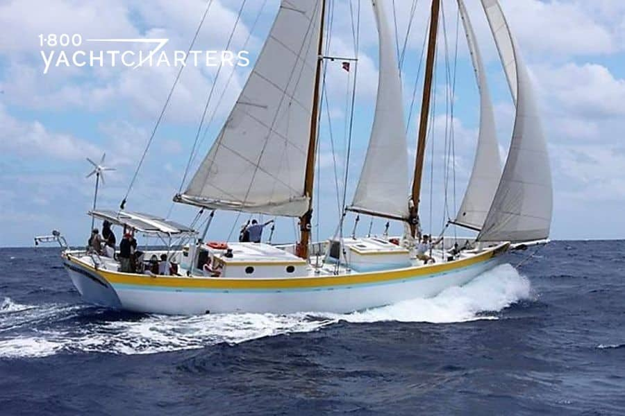 Profile photograph of sailboat, Jambalaya, underway in the Caribbean.  She is solid white with a yellow stripe around the top of the sailboat.  She is headed toward to upper right side of the photograph.