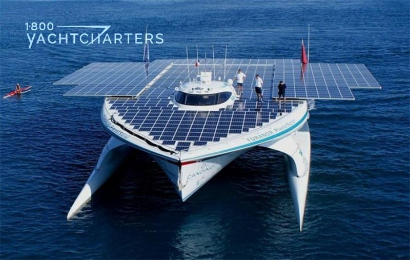 Aerial photograph of solar-powered catamaran, MS TURANOR. There are 4 people standing on her solar panels.
