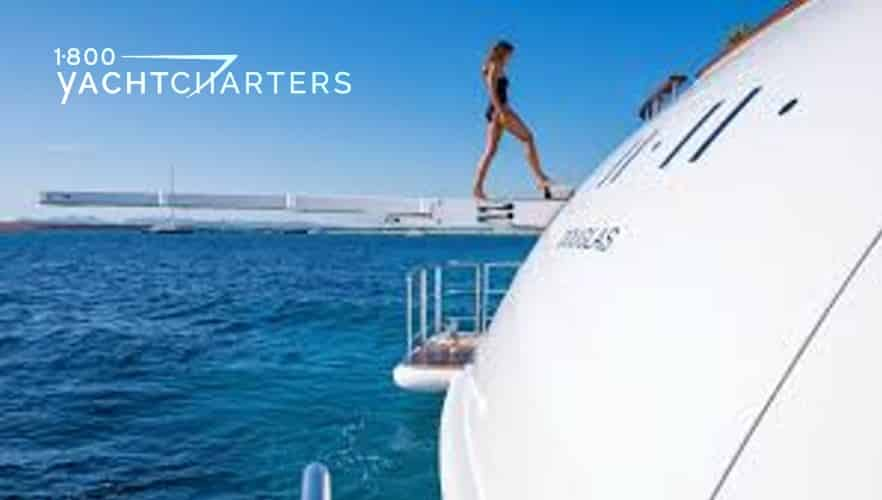 Photograph of a model in a black one piece swimsuit walking up the diving board, toward the boat, on a motoryacht