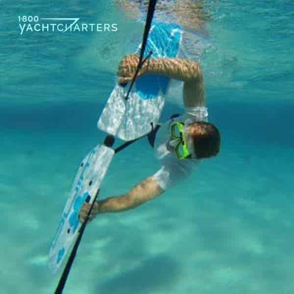 Underwater photograph of a person using a subwing. It is a watersports toy pulled by a boat. It looks like this person is holding onto a manta ray and being pulled underwater. He is wearing a lime green mask and clear snorkel. He is headed toward the bottom front of the photo, coming towards you.