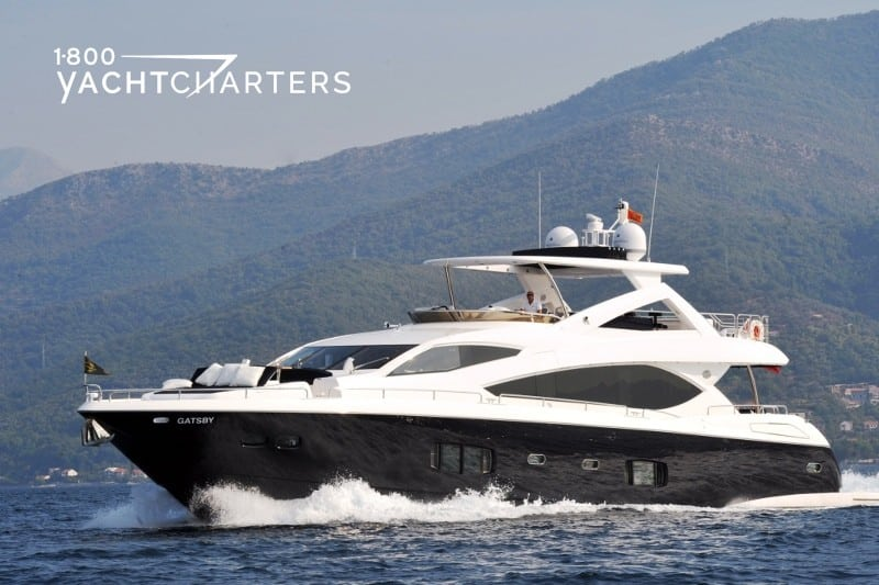 Profile photograph of Sunseeker 88 motoryacht Gatsby underway. Black hull, white superstructure. There is a mountain in the background. The yacht is headed toward the left side of the photograph.