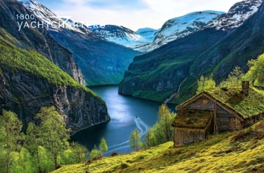 Photograph of fjord in Norway. Beautiful landscaping. Lush mountains beside a quiet river.  There is a wooden home on the hillside at the center, right side of the photo.