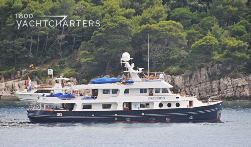 Profile photograph of superyacht POLYCARPUS at anchor. There are rocky cliffs and woods in the background. She has a blue hull and white superstructure.