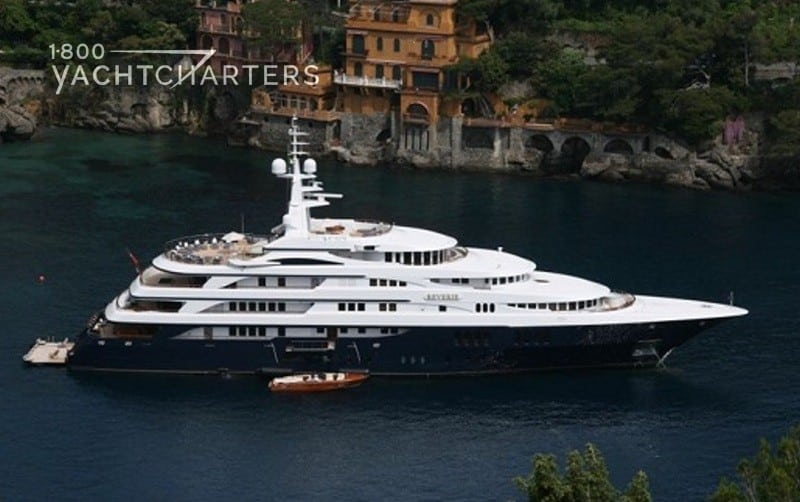 Aerial photograph of motoryacht REVERIE in Portofino.  The yacht has a dark blue hull and white superstructure. There is a small boat docked next to it.  The photograph looks down at the yacht at anchor. There are orange buildings in the background. Very peaceful photo.