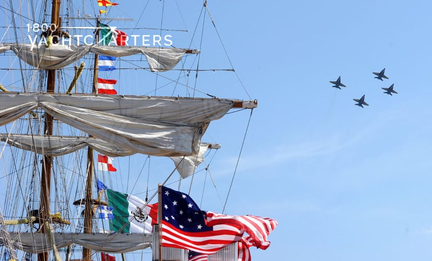 Photograph of tall ship mast covered in banner flags and the American flag.  In the background, the Blue Angels fly in formation in a beautiful blue sky.