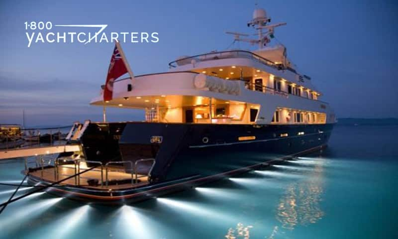 Photograph of a superyacht from the back profile. The photo is at night, and the yacht has underwater lights that illuminate all around the boat.