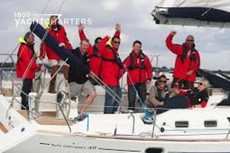 Photograph of men all wearing red jackets and standing and sitting on a sailboat that is underway. The men are waving at the camera. It is a team-building exercise on a boat. The yacht is headed toward the right side of the photo.