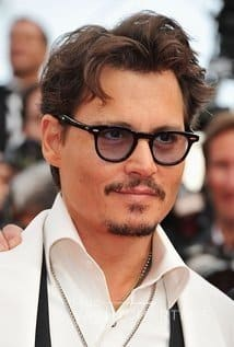 Photograph of yacht charter owner Johnny Depp. He is wearing black-rimmed glasses, he has a moustache and goatee, and he is smiling with closed mouth. It is only his head and shoulders in the photo. There is a crowd behind him.