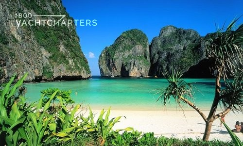 Photograph of Ko Phi Phi Don Island, Thailand, as seen from the land. Huge boulders in the water. Clean, clear green water. White sand beach. Palm tree.