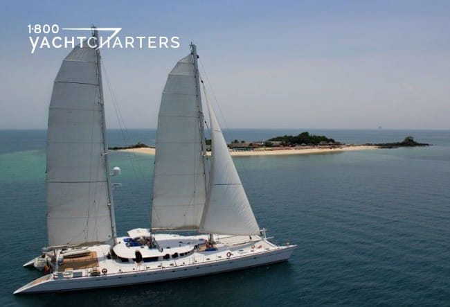 Aerial photograph of a sailing catamaran underway.  She is solid white.  There is an island surrounded by sand in the background of the photo. She is sailing toward the right side of the photograph.