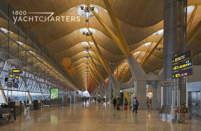 Photograph of the Madrid Barajas Airport terminal. It is spacious, with a shiny tile floor and bamboo ceiling and beams. The lighting glistens off of the floor and ceiling.