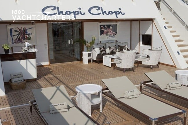 Photograph of the back of a yacht. The area is called the Beach Club. It is deck with chairs, a bar, and teak wood flooring. It is simply an additional room on the yacht.