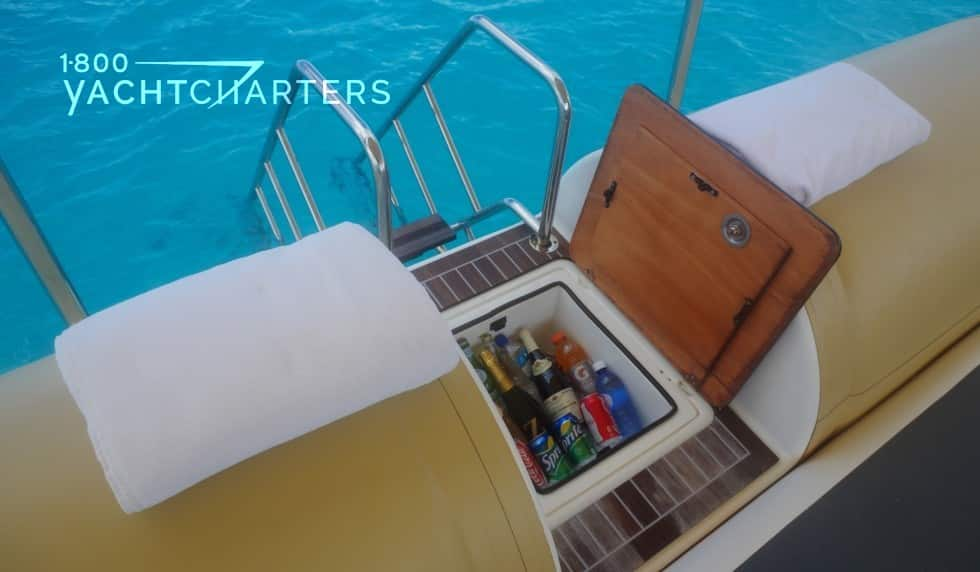 Photograph of an open refrigerated area of a floating sea cabana. The box contains multiple bottles of wine, and it has a teak lid that is open. There are golden yellow pontoons on both sides of the cooler, that form the sides of the floating pavillion. A silver and teak step ladder into the water leads down into the water from behind the cooler.